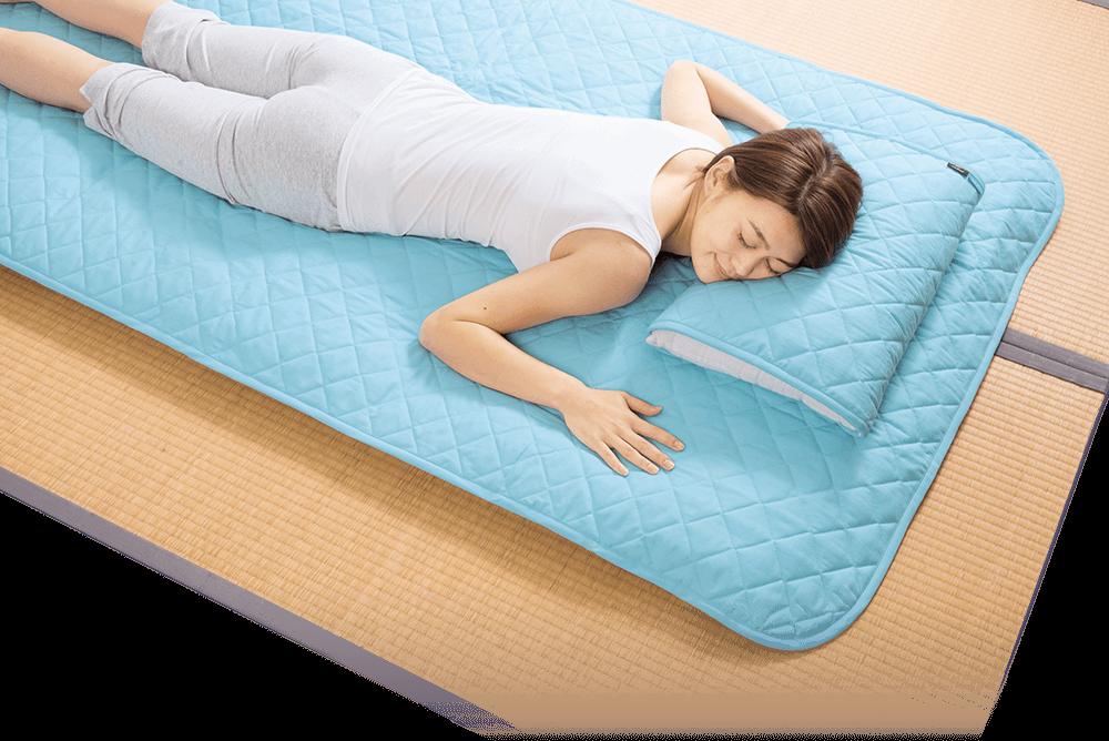 「クールアウト敷パッド」の商品画像 気持ち良さげに寝転ぶ女性の写真