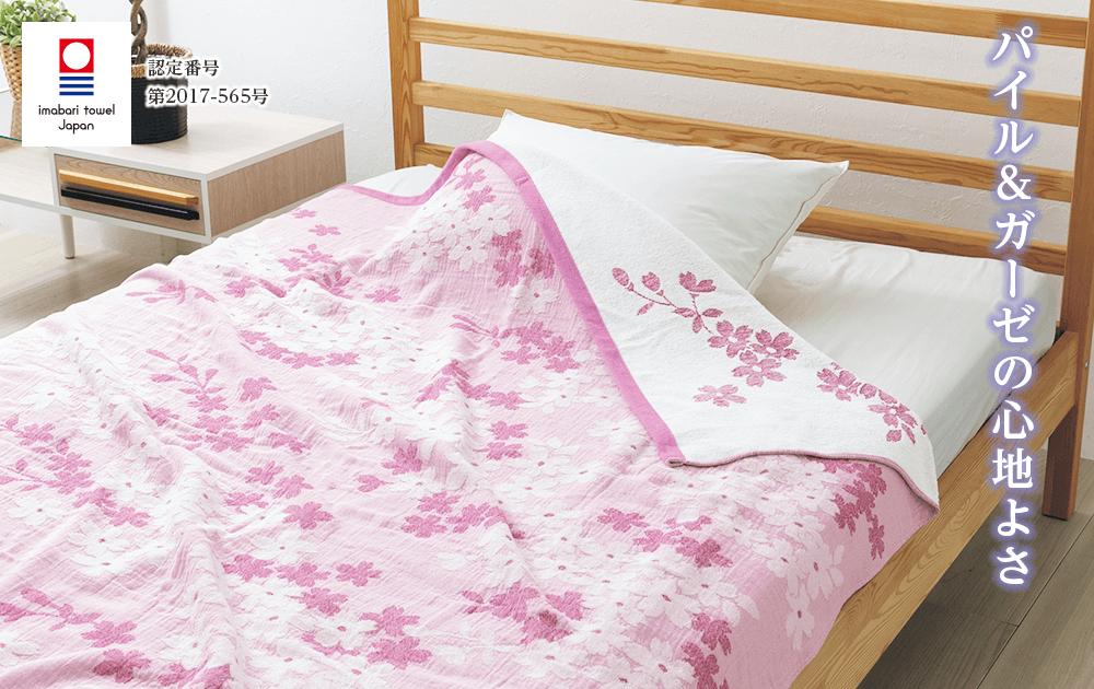 今治ブランドガーゼ同時織りタオルケットのメイン画像。ピンク色の桜柄タオルケットがベッドに敷いてある写真。