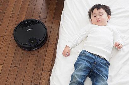 ベッドで寝ている子供の横を通るディーボットの写真
